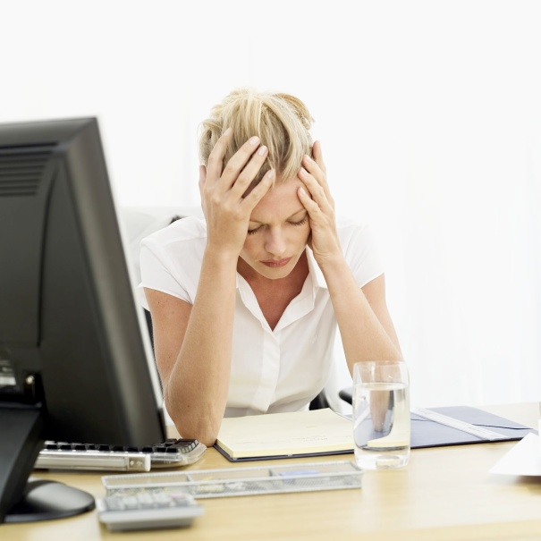 a woman sitting at a desk holding her head in pain